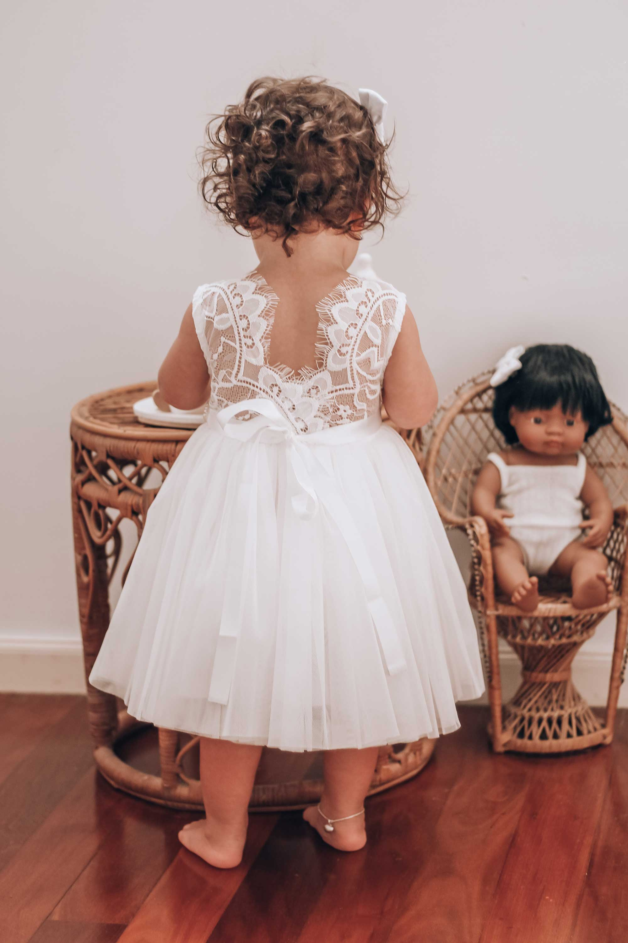 Kora showing the back of the White Chloe Lace Back Dress