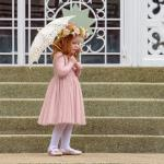 Young girl holding an umbrella in the Dusty Rose Chloe Dress